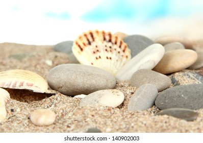 Sea stones on sand on bright background