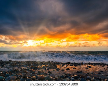 Sea storm with sun rays above sea waves and under dramatic cloudy sky