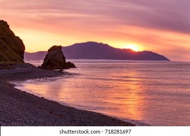 Sea sunset behind the island. The sea of Okhotsk, Koni Peninsula, Zavyalov island and Magadan region.