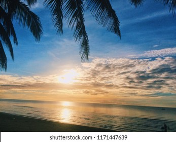 Sea at sunset blue sky sunlight with clouds and coconut tree people swimming in water landscapes