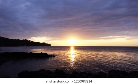 Sea sunset landscape. The orange sun is approaching the horizon and the evening sea gleams with gold paint in contrast to the dark cloudy sky. Camiguin, Philippines.