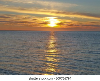 Sea sunset, sunny path on water, bright clouds