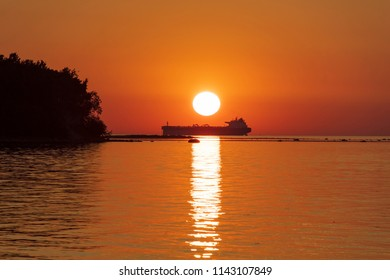 Sea Sunset View With Silhouette Of The Big Ship Near Coast