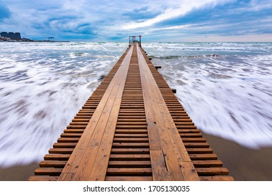 Sea surf after sunset, a wooden pier goes into the distance