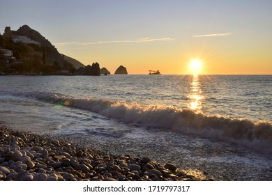 Sea surf, silhouettes of rocks on The black sea in the village of Gurzuf. The Golden color of the sky at dawn. Sunrise on the horizon. nature of Crimea, 2019