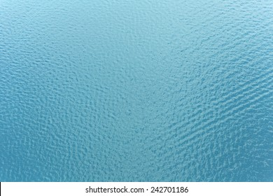 Sea surface background with ripple and reflection of sunlight from above