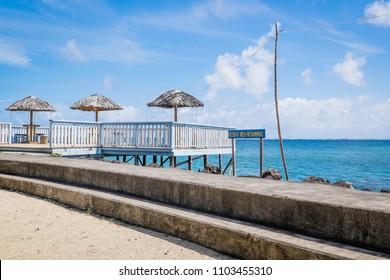 Sea swimming area and sun beach umbrellas by Piula Cave Pool, Upolu Island, Western Samoa, South Pacific