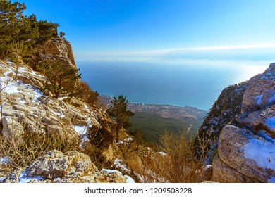 Sea through the gorge of mountains with a frosty sunny day, Ai-Petri mountain, Crimea, Russia. mountains, dry trees, pines on the top of a mountain