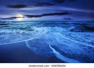 sea tide on a cloudy sunrise. green waves crashing golden sandy beach in full moon light. storm weather approaching. summer holiday concept