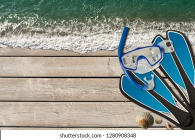 Sea vacation background. Ocean with waves on a wooden boardwalk with sand, seashells, scuba mask, flippers, snorkel and copy space