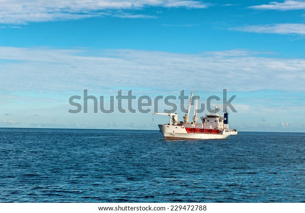Sea Vessel Sailing on Beautiful Blue Water Ocean at Seychelles Island with Lighter Blue Sky Background.