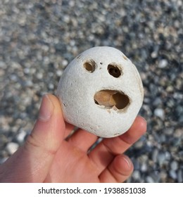Sea Stone with a Vexed Face in Hand Background of Sea Pebbles
