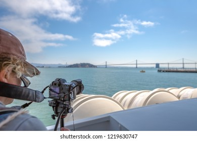 Sea view from boat to Alcatraz of photographer taking pictures of the San Francisco Financial District skyline with oakland bridge in California, United States.
