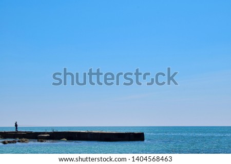Sea view from boat with crystal clear rippled Black sea's water and blue soft sky. No clouds or distracting elements. In the back people fishermen are catching goby fish on the relaxing calm weekend.