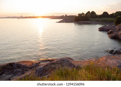 Sea view of the Gulf of Finland, summer evening and sunset at the rocky shore of the island of Suomenlinna in Finland.