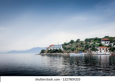 Sea view on the greek peninsula Pilion under a cloudy sky with mountains, a boat and some houses