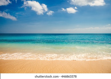 Sea view from tropical beach with sunny sky. Summer paradise beach of Bali island. Tropical shore. Tropical sea in Bali. Exotic summer beach with clouds on horizon. Ocean beach relax, outdoor travel