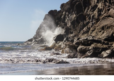 Sea water crashing on rock cliff on sunny day at the beach. Violent impact of wave on shore
