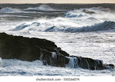 Sea water drains off large lava rocks with stormy seas slightly blurred in the background to set focus on the foreground elements.