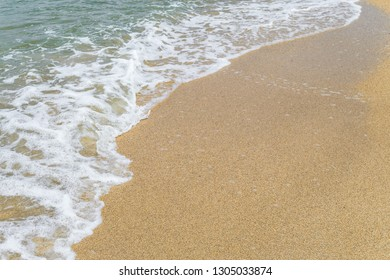 Sea water runs onto the sandy shore. Tidal water surf. Limited depth of field.