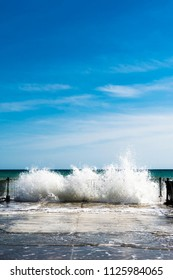 Sea water splashes at old pier