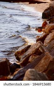 Sea water splashing against jagged brown rocks on the coastline