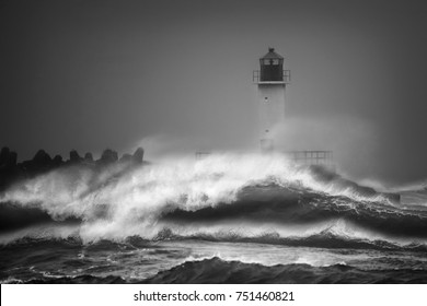 Sea water storm waves hitting stone pier and lighthouse in black and white autumn day light