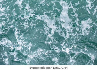 Sea water with white foam on surface, taken form top view angle.