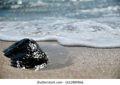 Sea wave is approaching the shore. White line made of foam and bubbles. Stone and sand bottom view very close blurred bokeh background. Sandy beach in the village of Znamenskoye, Spit Belyaus, Crimea.