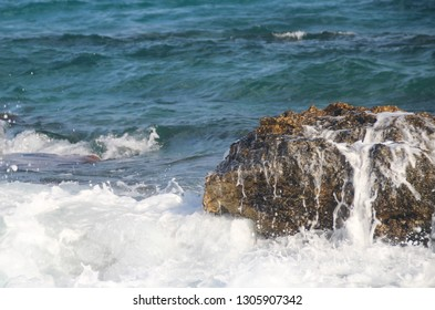 The sea wave breaks on a large stone on the shore with white splashes, clear sea, vacation at sea