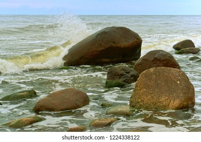 the sea wave breaks on the rocks, the waves are beating on the coastal boulders