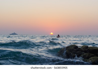 sea wave closeup at sunset time with red and orange sun reflection on the water. nature abstract blurred background. Phuket island, Thailand.