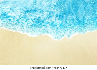 Sea wave on the sunny sandy beach.  View from top.