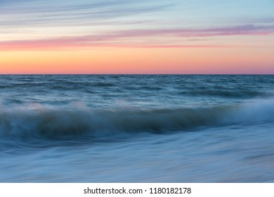 Sea wave rolls to the shore in the evening