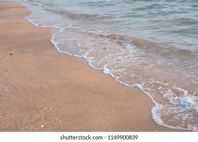 Sea wave, running on a sandy beach. Horizontal photo.