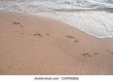Sea wave, running on a sandy beach washng away the footprints. Horizontal photo.
