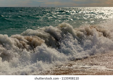 Sea wave with sand in Calella, Spain.