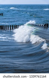 Sea wave splashing when overrun and hit row of wooden groin (copy space)
