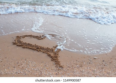 The sea wave that runs into the sandy beach is washing away the heart. Horizontal photo.