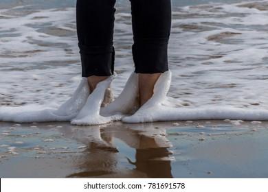 sea waves bathing a woman's feet on the beach. Guardamar del Segura, Spain