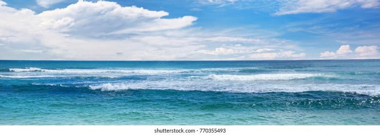Sea waves and blue sky. Wide seascape background.