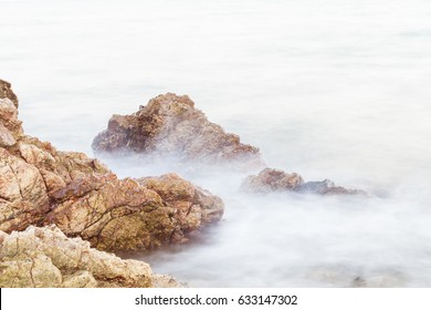 Sea waves breaking hit the rock at beach. Image may contain soft focus and blur due to long exposure