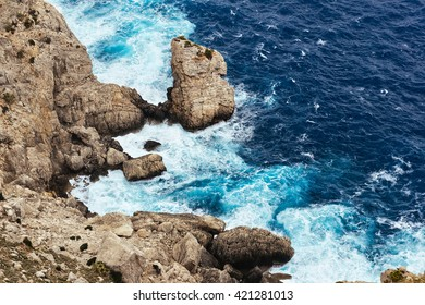 Sea waves breaking on a rocks in Majorca. Deep blue sea waves hit cliff. Sea waves hit rocks cliff. Mighty sea waves breaking on a cliff. Waves splashing over rocks. Strong ocean waves hitting rocks