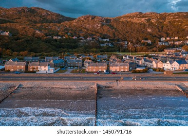 Sea waves breaking on the shore of scenic coastal town at stormy sunset. Barmouth in North Wales, UK