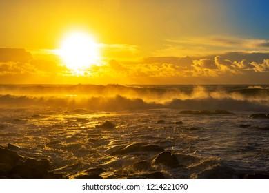 Sea waves and coastal rocks at golden sunset in Ancora coastline, Portugal