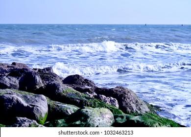 sea waves coming towards rocks with algae
