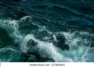Sea waves crashing against rocks. Turbulent blue and white water seascape background image.