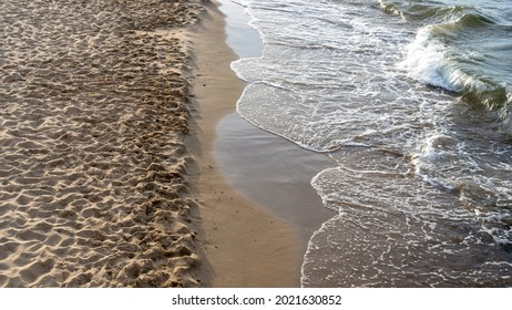 Sea waves crashing against the shore of a sandy beach at sunset. Baltic sea, Gdansk, Poland - Shutterstock ID 2021630852