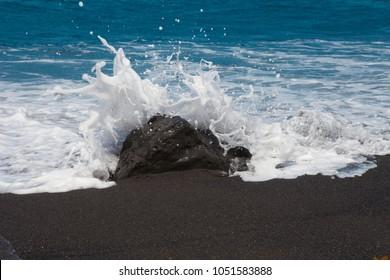 Sea waves crashing against the stone on the beach with black sand, Canary island