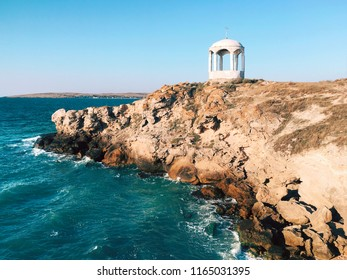 Sea waves crashing over rocks on wild stone beach. Blue sky over summer sea with sunlight reflection. Crimea, Black Sea